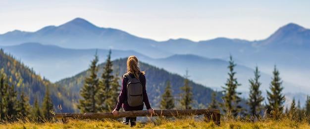 春の朝に常緑の森に覆われた壮大な霧のカルパティア山脈の息をのむような景色を楽しみながら壊れた木の幹の上に座ってバックパックで長い髪のブロンドの女の子の背面図。