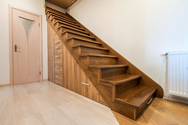 モダンな階建ての家で光沢のある木製の階段と豪華な廊下と近代建築インテリア。階段の下のスロットの滑走路にカスタム構築された引き出しキャビネット