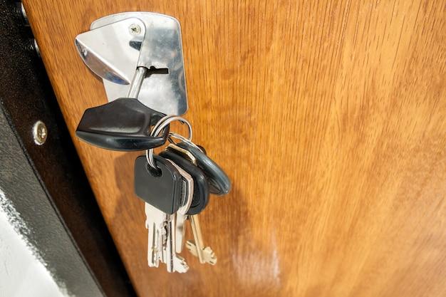 木製テクスチャドアの鍵穴にさまざまなキーの束のクローズアップ。