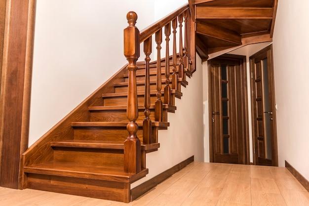 新しい改装された家のインテリアのモダンな茶色のオークの木製の階段とドア