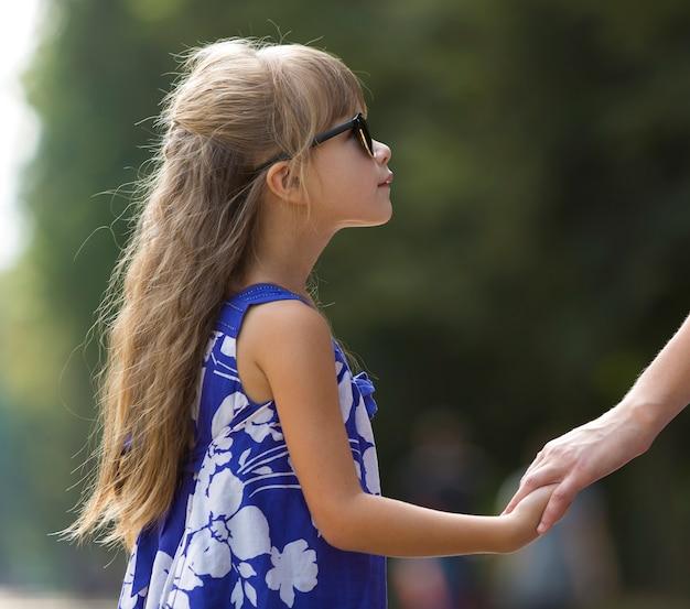 屋外の手を握って小さな子供の女の子。