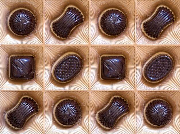Сладкие шоколадные конфеты ассортимент в коробке крупным планом. вид сверху