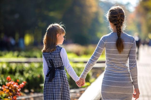 子供の女の子と一緒に手を繋いでいる母の背面図