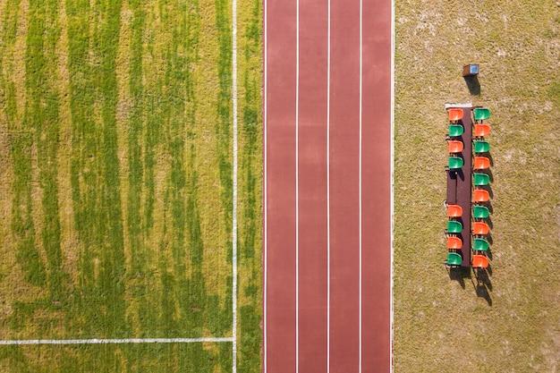 赤いランニングトラックと緑の草の芝生