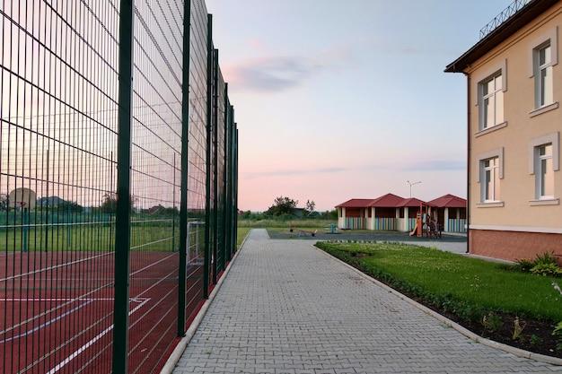 高い保護フェンスに囲まれたバスケットボールコートと就学前の建物の庭