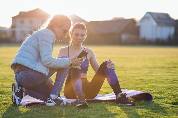 トレーニングマットの上に座ってスポーツ服の若い陽気な女性
