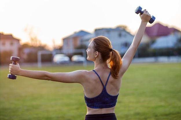 屋外で青いダンベル運動フィットネスウェアのアスレチック女の子