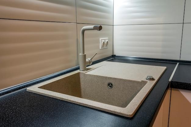 Гранитная раковина и водопроводный кран в новом современном интерьере кухни