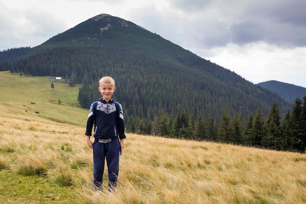 Ребенок мальчик с рюкзаком стоял в горной травянистой долине