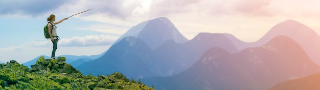 Молодая стройная блондинка туристическая девушка с рюкзаком указывает с палкой на туманную панораму горного хребта