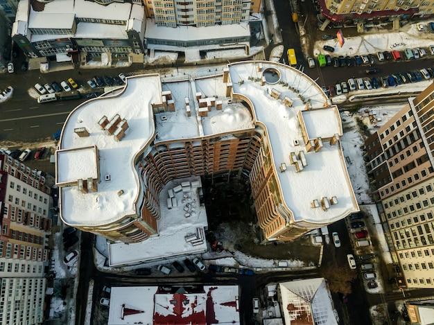 Воздушный черно-белый зимний панорамный вид сверху современного города с высокими жилыми комплексами зданий снежной крышей, припаркованных и движущихся автомобилей вдоль улиц. городская инфраструктура, вид сверху.