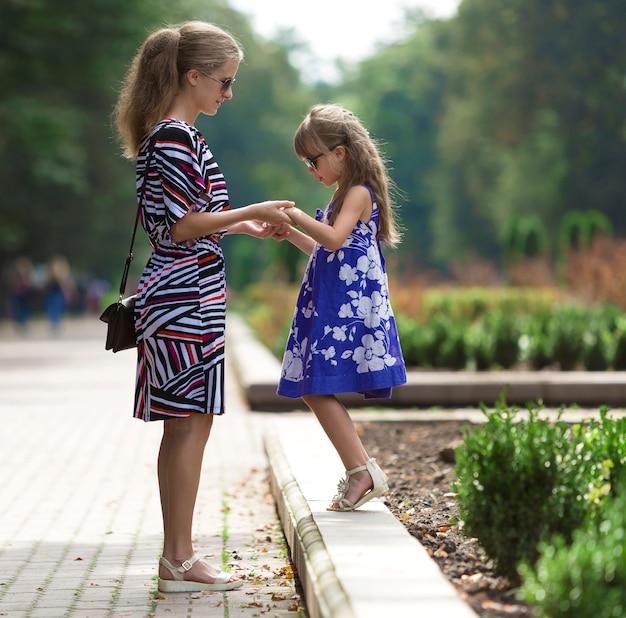 若いブロンドの女性と日当たりの良い公園の路地で手を繋いでいるファッショナブルなドレスの小さな子供の女の子。
