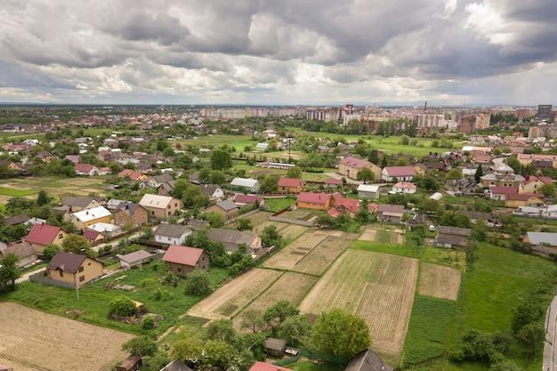 夏の緑の野原の間の建物と曲線的な通りの町または村の空撮。上から田舎の風景。