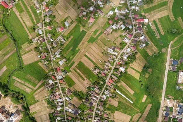 夏には、緑の野原の間の建物の列と曲線的な通りのある町または村の空中写真を上から見下ろします。上から田舎の風景。