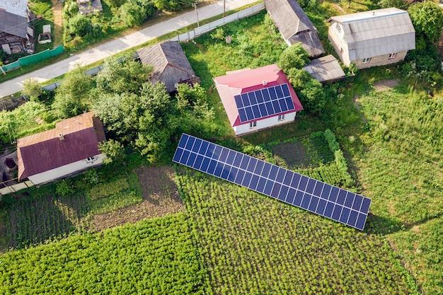 クリーンエネルギーの青い太陽電池パネルが付いている家の空撮。
