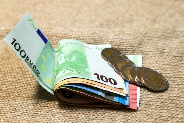 お金のユーロ硬貨と紙幣が異なる位置で互いに積み上げられて