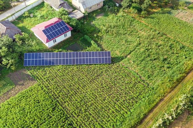 Вид с воздуха дома с голубыми панелями солнечных батарей для экологически чистой энергии.