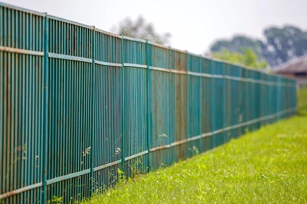 Длинный ржавый старый металлический забор.