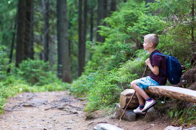 Ребенок мальчик с палкой и рюкзак, сидя в одиночестве