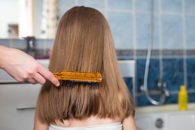 お風呂の後の子供の女の子の長い髪をとかすブラシで母の手