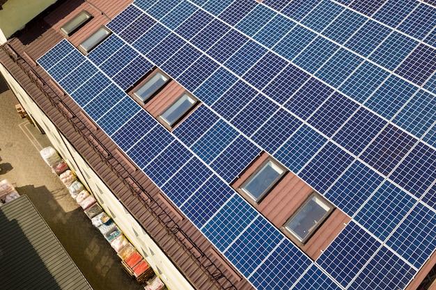 産業用建物の屋根に取り付けられた多くのソーラーパネルの空撮。