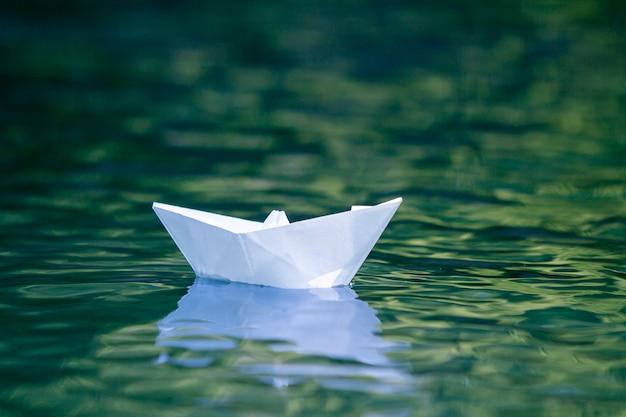 シンプルな小さな白い折り紙の紙の船のクローズアップ