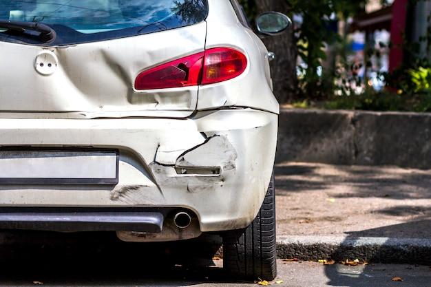 道路上の事故により破損した白い車の背面