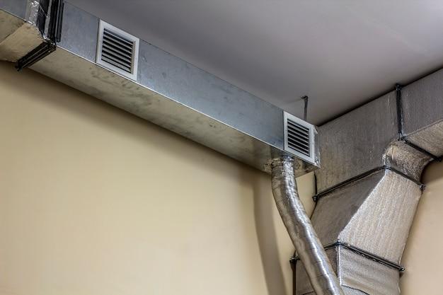 産業用建物の天井に設置された産業用エアダクト換気装置とパイプシステム。