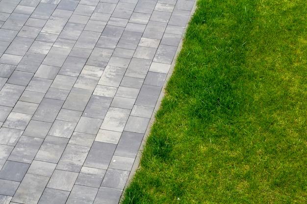 灰色のタイルと屋外の緑の草