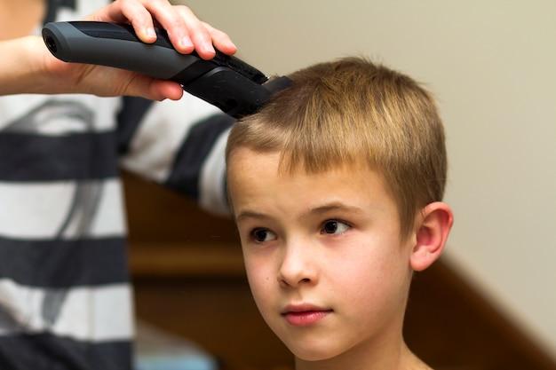 美容師は理髪店で子供男の子の髪をカットします。