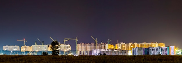 Панорама ночной вид многих строительных кранов на строительной площадке нового современного жилого района