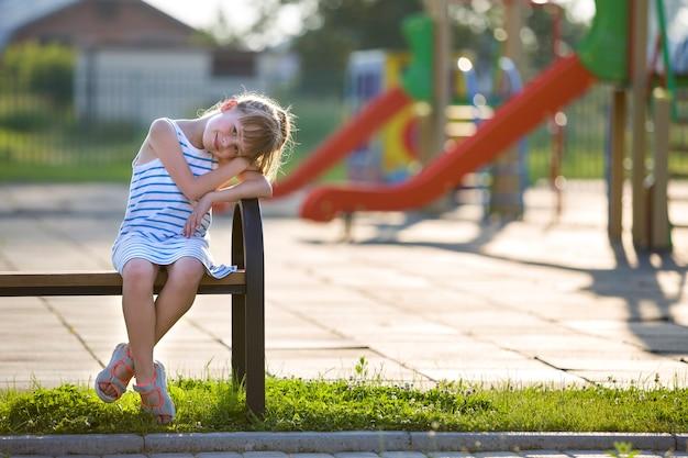 遊び場のベンチに一人で屋外に座って短いドレスでかわいい若い女の子