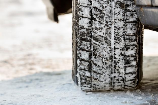 深い冬の雪道で車の車輪のゴム製タイヤのクローズアップ