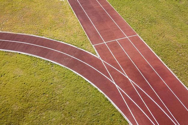 Красные беговые дорожки и зеленая трава газон