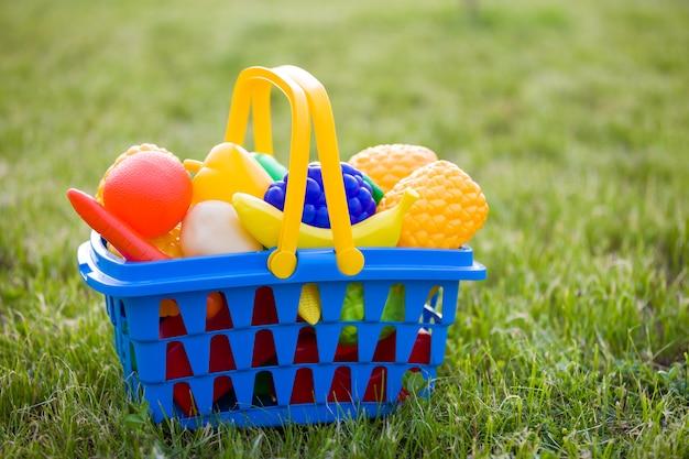Яркая пластиковая красочная корзина с игрушечными фруктами и овощами на улице в солнечный летний день