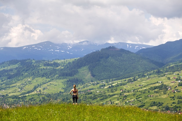 日当たりの良い夏の日に緑の山々の背景に草が茂った谷に立っているスリムな若い女性