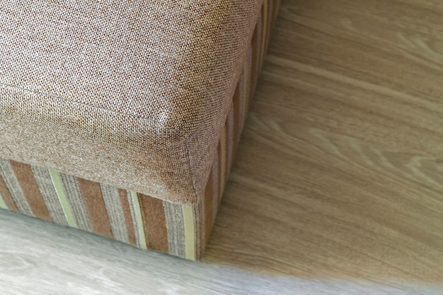 木製の寄せ木張りの床のリビングルームでモダンなベージュテクスチャソファ