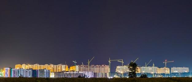 新しいモダンな住宅地の建設現場で多くの建物クレーンのパノラマ夜景