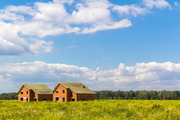 Современные дома строятся в зеленом поле в солнечный день