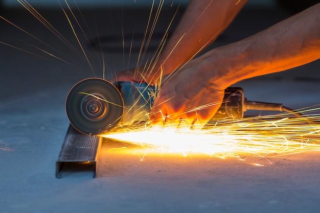 グラインダーで金属を切断する労働者の手のクローズアップ。鉄を粉砕しながら火花。低い焦点深度
