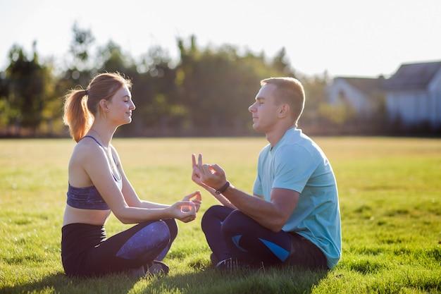 屋外楽しんで若いカップル。男と女が日の出で緑の芝生とフィールドで外で一緒に瞑想します。