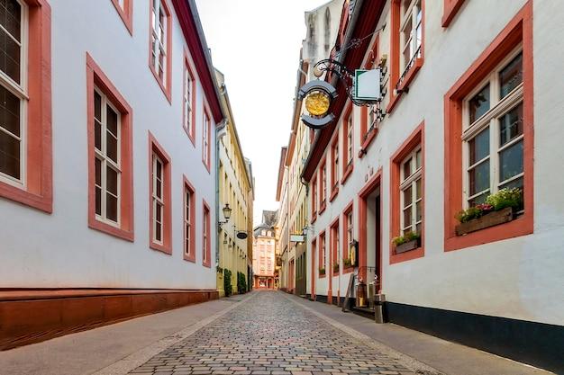 歴史的な伝統的な家屋とヨーロッパの旧市街の石畳の通りの狭い道