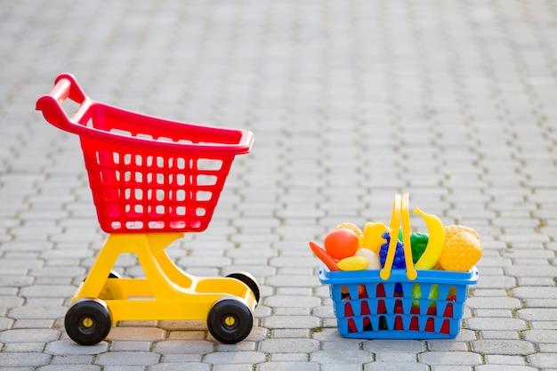Торговая тележка и корзина с игрушечными фруктами и овощами.
