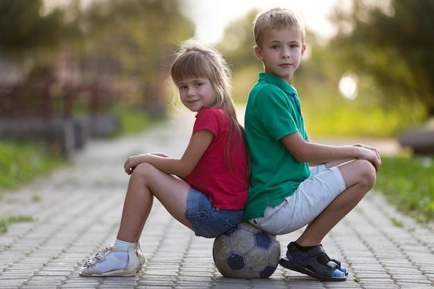 Детский мальчик и девочка сидят на футбольном мяче