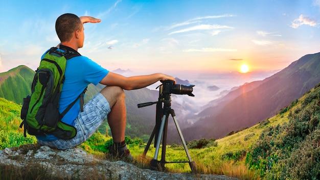 岩の上に座っているハイカーカメラマン