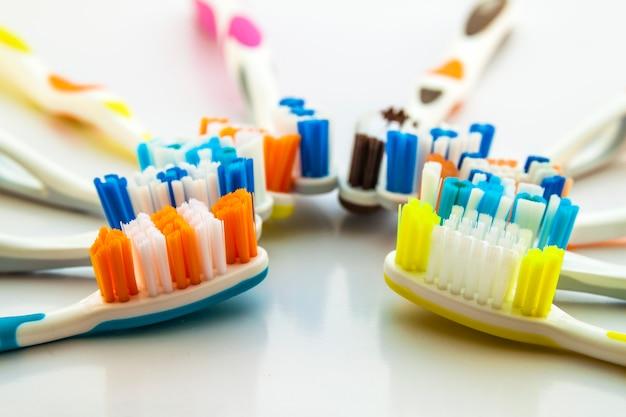 白い背景に、概念歯科のきれいなトイレに色とりどりの歯ブラシのセットのショットを閉じる。