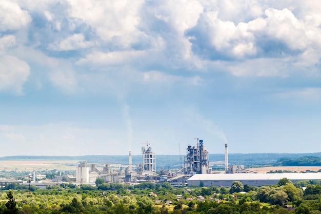 Промышленный цементный завод с дымящимися трубами и надутыми облаками