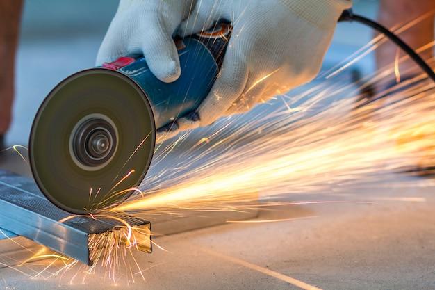 Конец-вверх инструментального металла работника с точильщиком. искры при шлифовании железа.