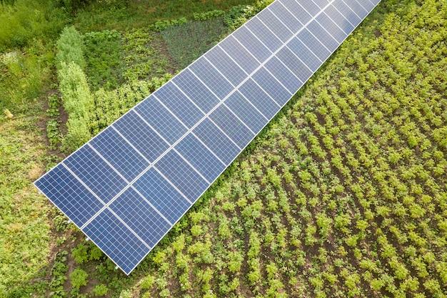 緑の芝生のクリーンエネルギーの青い太陽電池パネル。