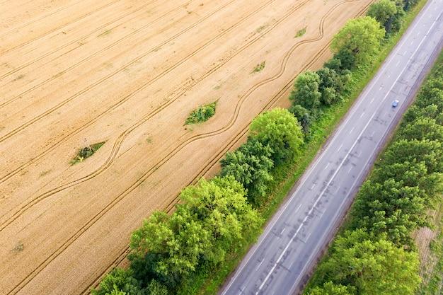 Вид с воздуха дороги между желтыми пшеничными полями и зелеными деревьями.